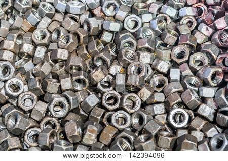 Top view of big pile of screw nuts as background