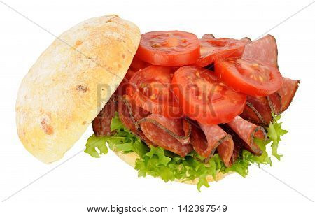 Spicy salami and tomato sandwich in a crusty bread roll isolated on a white background