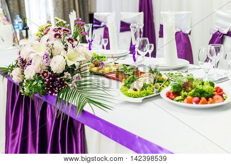 food table decorated with purple and white beautifu flowers for wedding