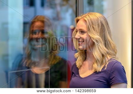 Smiling Young Woman Reflected In A Store Window