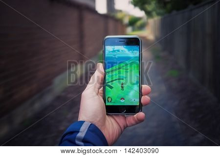Male Hand Holding Iphone 6 With Pokemon Go