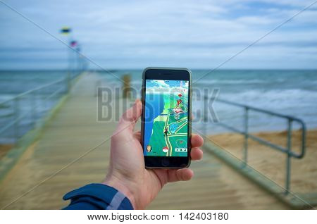 Male Hand Holding Iphone 6 With Pokemon Go On A Pier