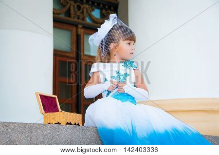 Cute little girl in a holiday white and blue dress is sitting on the steps near the columns