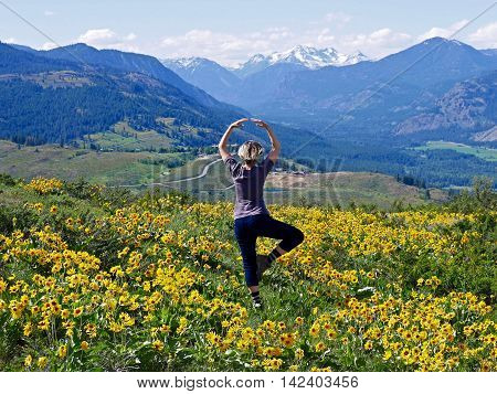 Slim blond woman exercising in meadows fillde with flowers.  Patterson Mountain near Winthrop WA USA. North Cascades National Park.