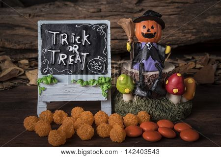 Pumpkin head jack (Jack-o-lantern) in witch suit sitting on a tree with trick or treat board and orange candy over forest background