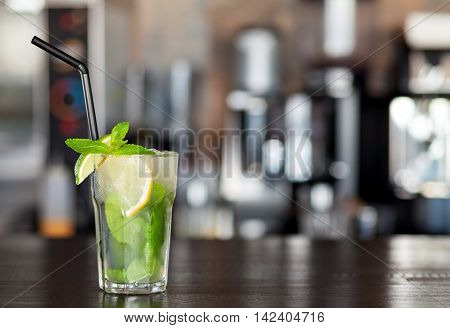 Lemonade with lime, mint on the background of the bar in the cafe. Summer drink.