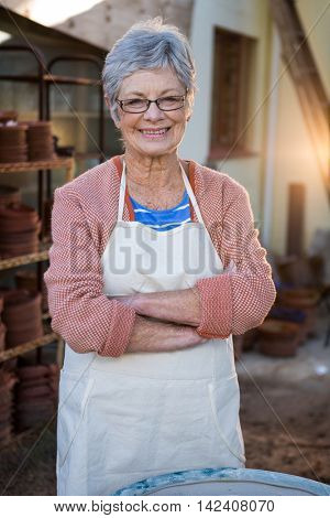 Happy female potter standing with arms crossed in pottery workshop