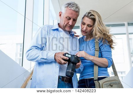 Front view of mature couple holding camera at home