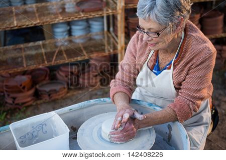 Female potter making pot in pottery workshop