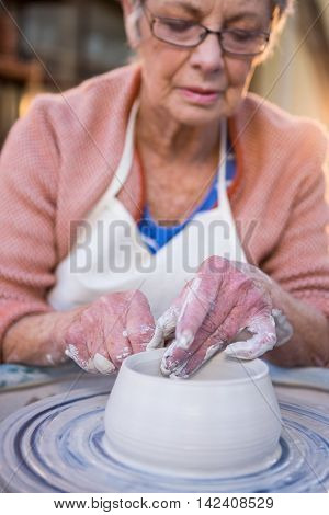 Close-up of female potter making pot in pottery workshop