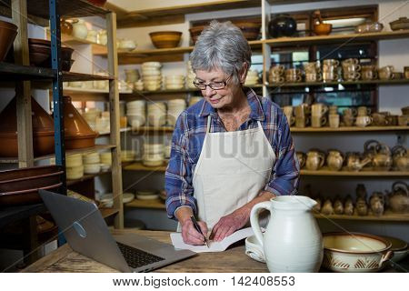 Female potter making note from laptop in pottery shop