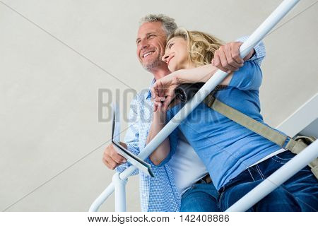 Low angle view of thoughtful mature couple by railing at home