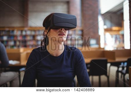 Mature student using virtual reality headset to help with studying in college library