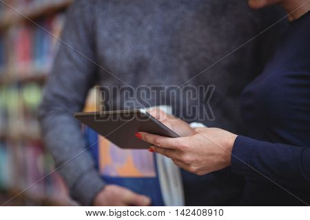 Mid section of mature students using digital tablet in college library