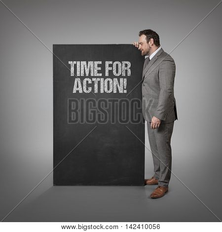Time for action text on blackboard with businessman standing side
