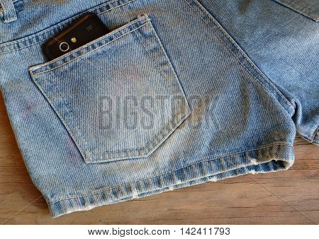 cell phone in back pocket of short blue jean pant on wooden board