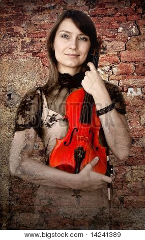 Beautiful female violinist with violin on the grunge background