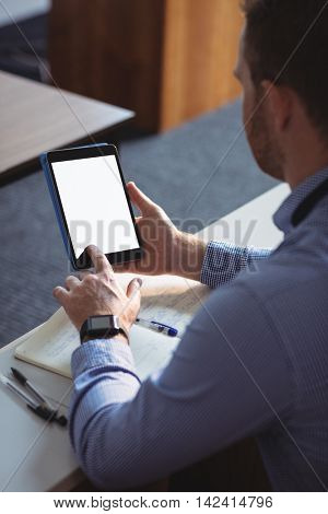 Mature student using digital tablet in the classroom