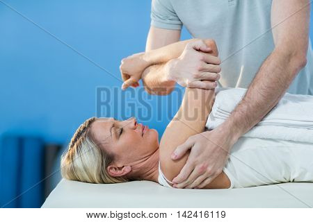 Woman receiving shoulder therapy from physiotherapist in clinic
