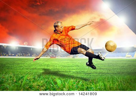 Happiness football player after goal on the field of stadium with blue sky
