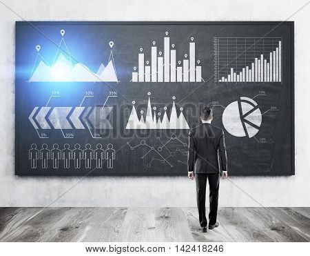 Rear view of man in suit standing in office in front of blackboard with graphs and sketches analyzing data. Concept of stats. Toned image.