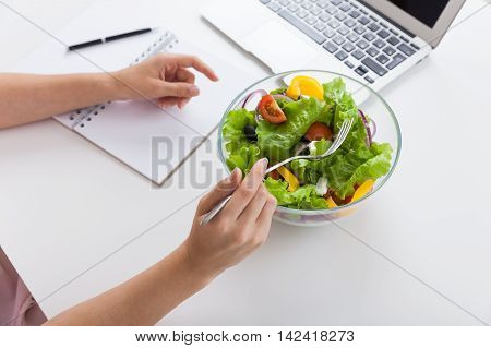 Woman eating her salad during lunch break at her desk in office. Bowl of colorful and healthy salad on table. Concept of enjoying good lifestyle. Top view.
