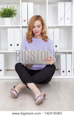 Woman in casual clothes sitting on floor with legs crossed working with her large tablet. Concept of comfort at work