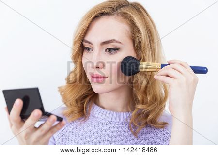 Girl in purple sweater applying powder to her beautiful face and looking at herself in little mirror. Concept of beauty and glamour