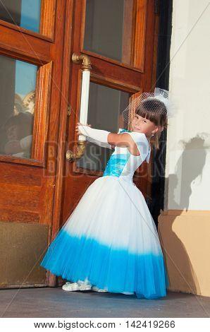 Schoolgirl in blue and white smart dress near the wooden door