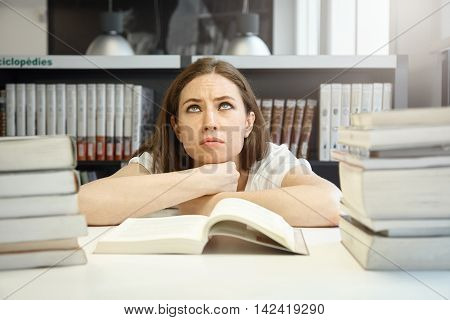 Angry Caucasian Female Student With Tense Eyebrows Looking Up, Trying To Prepare For Examinations An