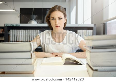 People And Education Concept. Tired Female Student Studying, Reading Textbook On Economics, Preparin
