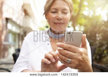 Portrait Of Attractive Mature 60-year Old Woman With Blond Hair Holding Smart Phone, Messaging Via S