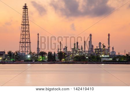 Oil refinery river front during sunrise, heavy industry background