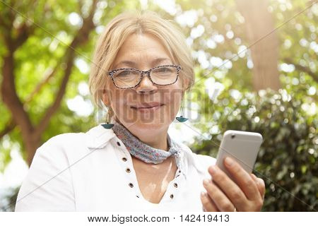 Headshot Of Beautiful Caucasian Female Pensioner Looking At Camera With Happy Cheerful Expression Wh