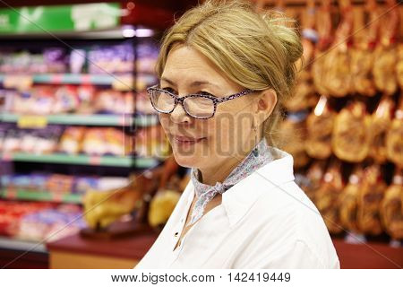 Half Profile Portrait Of Tired Middle-aged Woman With Fair Hair At Supermarket Dressed Casually Reme
