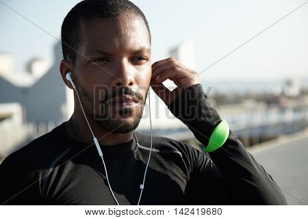 Close-up Shot Of Young Black Man With Beard Putting Headphone In His Ear. Determined Sportsman Is Re