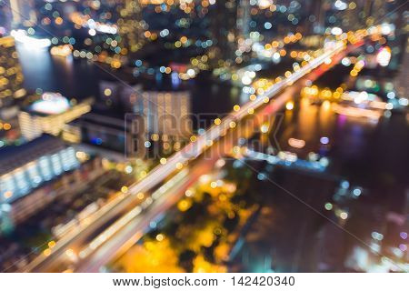 Blurred bokeh lights city bridge cross river, abstract background