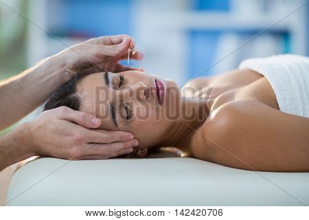 Male physiotherapist giving head massage to female patient in clinic