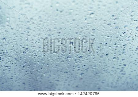 Background of rain drops on glass, tilt shift, toned blue
