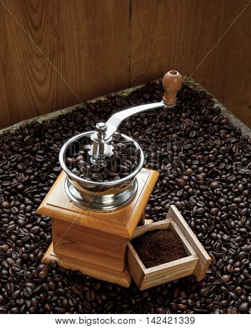 Coffee grinder and fresh grinded coffee beans on wooden background