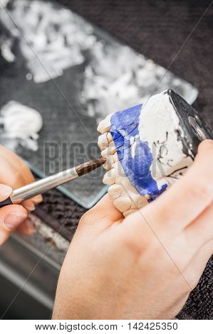 Dental technician working on dentures , denture concept