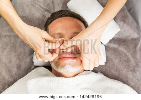 Male face with cream mask hands of professional cosmetologist with cotton sponge massage