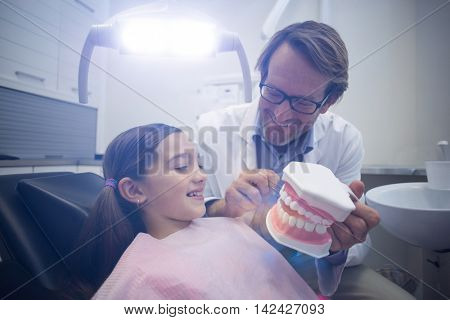 Dentist showing model teeth to patient in dental clinic