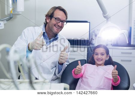 Portrait of smiling dentist and young patient showing thumbs up in dental clinic