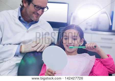 Dentist assisting young patient while brush teeth in dental clinic