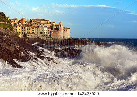 Tellaro village with the Church of St. George (San Giorgio) with cliffs and white sea waves. La Spezia Liguria Italy