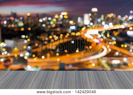 Opening wooden floor, blurred lights highway interchanged with city downtown
