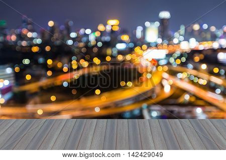 Opening wooden floor, abstract blurred highway interchanged with city downtown background