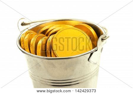 Macro view of metal bucket with gold coins isolated on white background