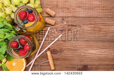 Homemade white wine sangria with fresh berries on a wooden table.
